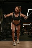 Une femme aux cheveux blonds fait un entraînement de poitrine sur la machine à câble dans une salle de sport photo