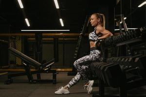 Une photo du côté d'une femme en forme qui est assise sur une rangée d'haltères dans une salle de sport