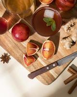 oranges, gingembre et cocktail sur une planche à découper photo
