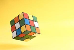 un cube de rubik volant sur fond jaune photo