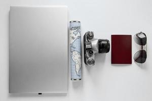 passeport, carte, appareil photo et autres articles de voyage sur fond blanc