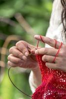 Mains d'une femme qui crochète avec des tricots de laine rouge devant un arrière-plan flou photo