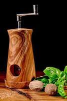 Moulin à muscat sur planche de bois avec feuilles de basilic, tomate, piment et muscade photo