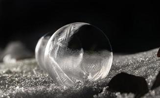 Détail d'une bulle de savon gelée sur un sol enneigé pendant la nuit photo