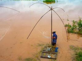 pêcheur dans le mékong avec des outils de pêche anciens photo