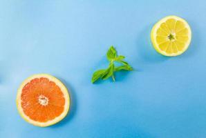 Pamplemousse et tranches de citron et feuilles de menthe sur fond bleu photo