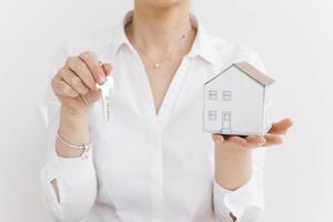 Woman holding key sand mall papier maison sur fond blanc photo