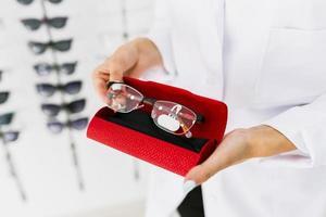 femme tenant un étui rouge avec des lunettes photo