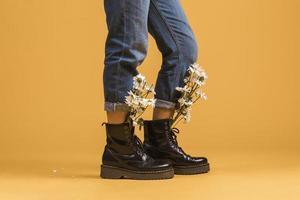 Les jambes de la femme portant des bottes avec des fleurs à l'intérieur sur fond orange photo