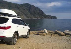 une grande voiture blanche devant la mer. photo