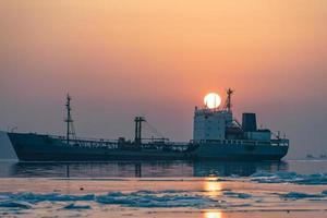 marin avec bateau de pêche sur fond de coucher de soleil. photo