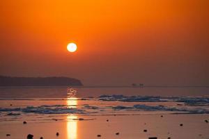 plage de glace de paysage marin et le coucher de soleil rouge. photo