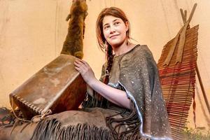 jeune fille lakota est assise dans un tipi et fait une boîte en cuir brut photo