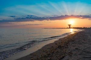 magnifique coucher de soleil sur fond de mer et antenne spatiale. photo