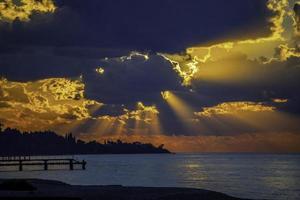 paysage marin avec un coucher de soleil brillant et des rayons à travers les nuages photo