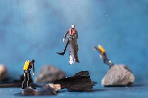 Les gens miniatures, les plongeurs nettoient la pollution des déchets plastiques jetés dans l'océan, le concept de pollution sous-marine photo