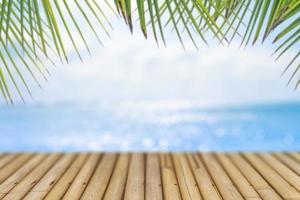 mise au point sélective de la vieille table en bois avec une belle plage floue avec des palmiers tropicaux pour afficher votre produit. photo