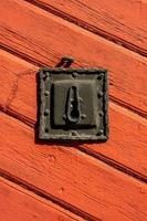 Ancienne serrure de porte en fer sur une porte en bois rouge photo