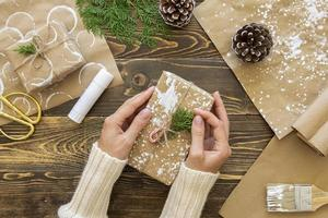 Vue de dessus mains tenant un cadeau de Noël avec des plantes et des pommes de pin photo