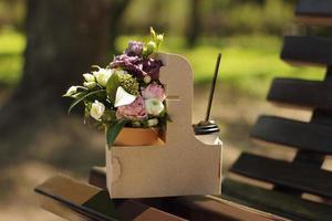 bouquet et café à emporter sur un banc de parc photo