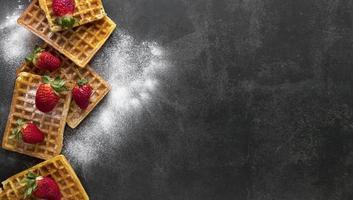 vue de dessus gaufres avec sucre en poudre et fraises photo