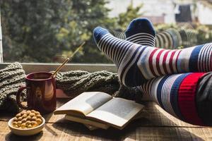 jambes portant des chaussettes rayées près de la fenêtre photo