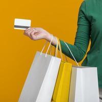 Femme tenant une carte de crédit et de nombreux sacs à provisions sur fond orange photo