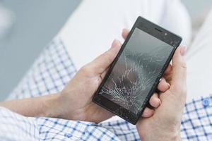 Vue aérienne de la femme tenant un écran d'affichage mobile cassé photo