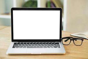 Ordinateur portable avec écran blanc vierge avec des lunettes sur un bureau en bois photo