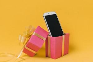 téléphone portable avec écran blanc et boîte-cadeau rose sur fond jaune photo