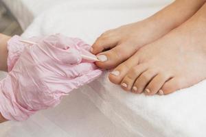 pédicure portant des gants de protection tout en travaillant sur les pieds photo