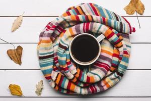 écharpe avec des feuilles d'automne couché autour du café photo