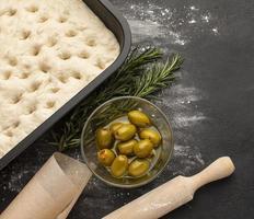 vue de dessus pâte de focaccia et olives photo