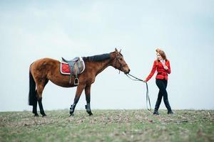 Fille jockey aux cheveux roux dans un cardigan rouge et des bottes noires avec un cheval photo