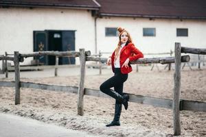 Fille jockey aux cheveux roux dans un cardigan rouge et des bottes hautes noires photo