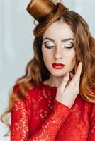 jeune fille aux cheveux rouges dans une robe rouge vif dans une pièce lumineuse photo