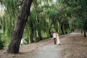 un mec et une fille marchent le long des rives d'une rivière sauvage envahie par la végétation photo