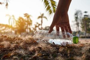 personne ramassant une bouteille en plastique photo