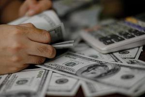 personne comptant de l & # 39; argent avec une calculatrice photo