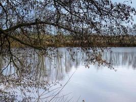 Vue sur un lac à travers des branches d'arbres à North Cave Wetlands dans l'East Yorkshire en Angleterre photo