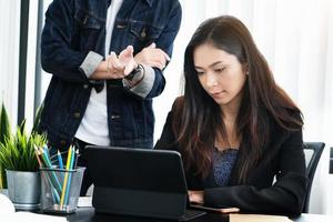 femme travaillant sur une tablette avec un homme qui parle derrière elle photo