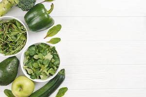 vue de dessus vert légumes frais sains bureau en bois blanc. beau concept de photo de haute qualité et résolution