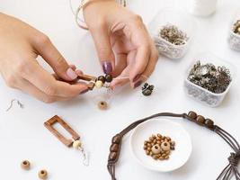 femme faisant des accessoires avec des perles en bois. beau concept de photo de haute qualité et résolution
