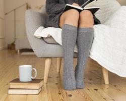 femme portant des chaussettes de genou assis fauteuil. beau concept de photo de haute qualité et résolution