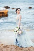 mariée avec un bouquet de fleurs sur la plage photo