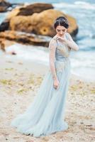 mariée dans une robe de lumière bleue marchant le long de l'océan photo