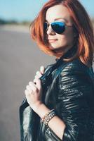 fille aux cheveux rouges dans une veste noire et des lunettes bleues photo