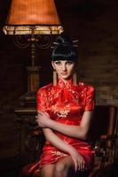 Fille dans une robe de soie japonaise rouge qipao dans une pièce sombre photo
