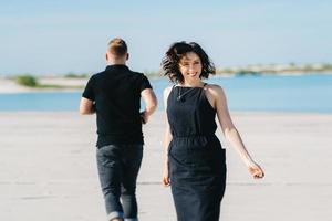 jeune couple un mec avec une fille en vêtements noirs marchent sur le sable blanc photo