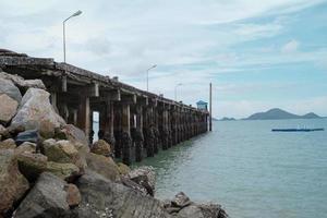 route en béton dans la mer avec paysage et île en arrière-plan. paysage marin et la structure portuaire dans la mer. photo
